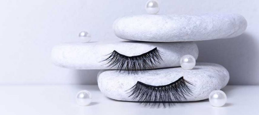 Black fake eyelashes against white cotton pads.