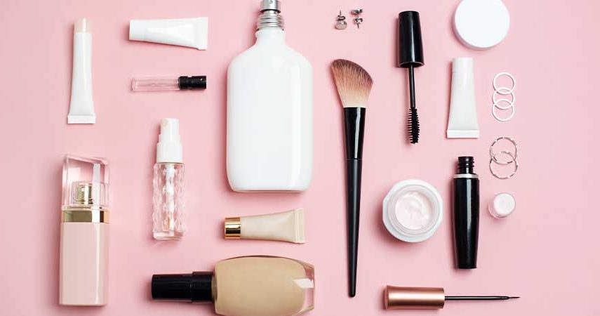 Perfume, makeup brushes and foundation against a pink background.
