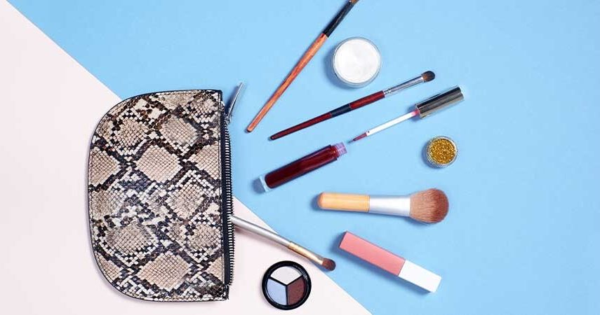 A picture of an open makeup bag with different makeup and makeup tools spread out in front of it.