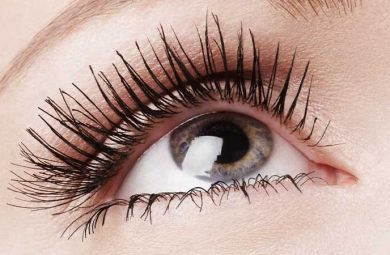 A close up photo of a person's eye and eye lashes wearing mascara