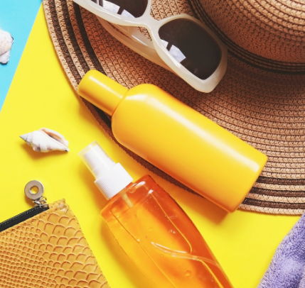 A photo of beachwear items, including a sun hat, sunglasses, the edge of a towel, the edge of a zippered bag, three seashells, and two bottles. One bottle is a yellow opaque and the second is a transparent yellow with clear liquid inside.