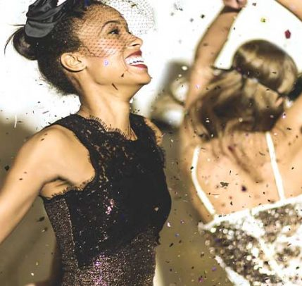 Two women wearing sequin dresses dancing at a party.