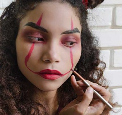 A girl painting her face with red makeup.